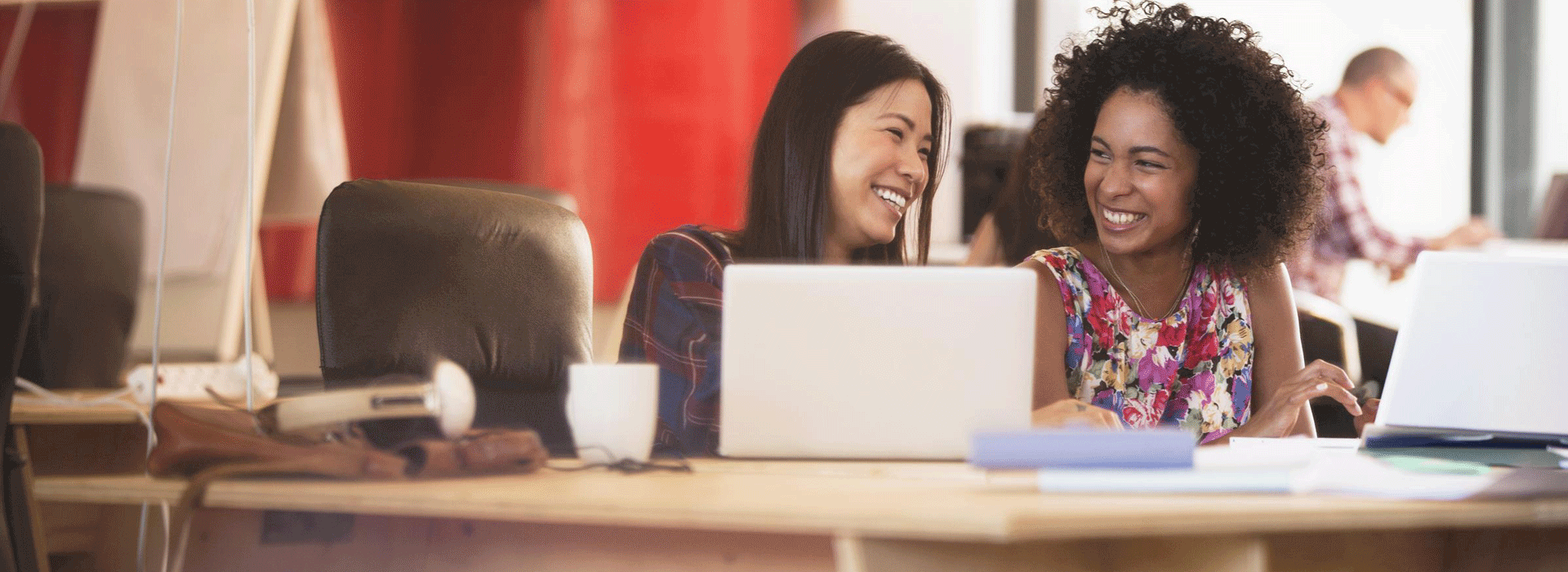 Two woman working on their laptops in an office environment laughing with each other